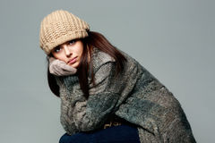 Pensive woman in warm winter outfit on gray background Stock Photos