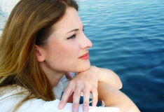 Pensive Woman By Water. Closeup portrait of a beautiful woman with a pensive expression in profile, looking out toward water Stock Photo