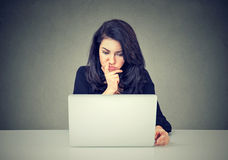 Pensive woman working on laptop computer stock image