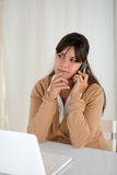 Pensive woman working and speaking on cellphone. Portrait of a pensive woman working and speaking on cellphone in front of her laptop computer Royalty Free Stock Photo