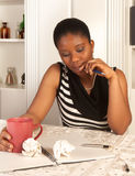 Pensive woman writing. Pensive african woman writing a letter at home Stock Photography
