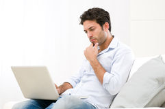 Pensive worried guy at laptop Royalty Free Stock Photography