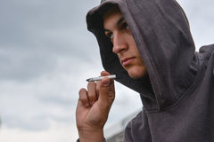 Pensive and worried teenage boy with black hoodie is smoking cig Royalty Free Stock Photography