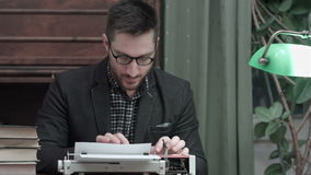 Pensive writer sitting in front of typewriter thinking of new ideas for his book stock footage
