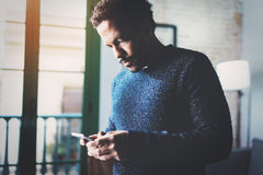 Pensive young African freelancer typing screen of mobile phone while working in new project at home.Black man looking Royalty Free Stock Image