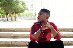 Pensive young african man sitting on steps Stock Photo