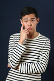 Pensive young Asian man looking at camera Royalty Free Stock Photos