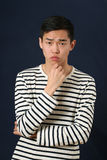 Pensive young Asian man looking at camera Royalty Free Stock Photo