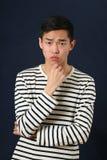 Pensive young Asian man looking at camera Royalty Free Stock Photo