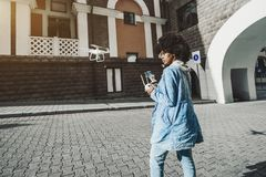 Black girl operating drone with remote device stock photography