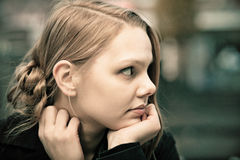 Pensive young blond woman. Profile of a pensive young blond woman, desaturated, film grain Royalty Free Stock Photography