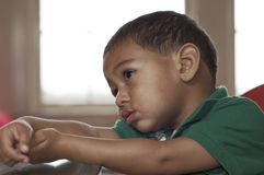 Pensive young boy. A young mixed-race child sitting at the table by a window seemingly in thought Stock Photography