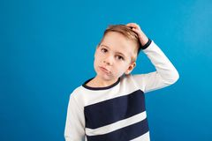 Pensive young boy in sweater touching his head Royalty Free Stock Photo