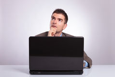 Pensive young business man behind laptop looks away Royalty Free Stock Image