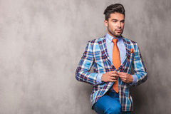 Pensive young business man closing his jacket. Stock Photo