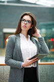 Pensive young business woman holding tablet computer Stock Image