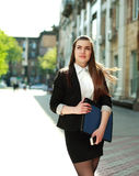 Pensive young business woman is walking on a street Royalty Free Stock Photos