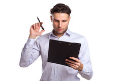 Pensive Young Businessman Holding A Tablet And Pen Royalty Free Stock Photography