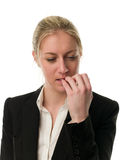 Pensive young businesswoman biting her nails. Isolated on white background stock photography