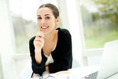 Pensive young businesswoman. Looking at the camera with a smile and thoughtful expression as she sits at a table in a bright sunny room with her laptop computer Royalty Free Stock Photos