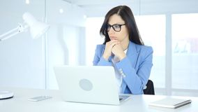 Pensive Young Businesswoman Thinking and Working on Laptop. 4k , high quality Royalty Free Stock Photos
