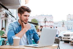 Pensive young casual man looking at laptop in cafe outdoors Stock Images