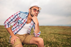 Pensive young casual man sitting on a chair outdoor Stock Image