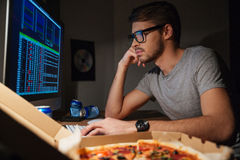Pensive young developer in glasses coding at home Stock Photos