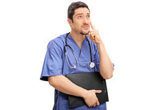 Pensive young doctor holding a clipboard Royalty Free Stock Photography