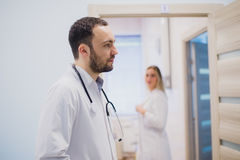 Pensive young doctor in white coat holding diagnosis in hospital, caring doctor concept Stock Image