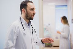 Pensive young doctor in white coat holding diagnosis in hospital, caring doctor concept Stock Photo
