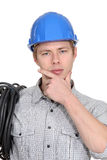 Pensive young electrician. Wearing a blue hard hat Royalty Free Stock Image