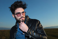 Pensive young fashion man with beard and glassess. Looking away from the camera Royalty Free Stock Photos