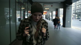 Pensive young fashion woman with backpack walking in the city, steadicam shot stock video