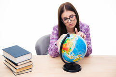 Pensive young female student sitting with globe Royalty Free Stock Photo