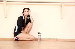 Pensive young fit woman leaning on the wall Stock Photos