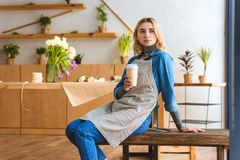 Pensive young florist holding paper cup and looking away. In flower shop stock image