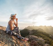 Pensive young girl in headphones enjoying beautiful sunset on the top of a mountain. California, USA Royalty Free Stock Photo