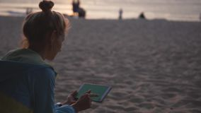 Pensive young girl using a tablet and sitting on the beach at sunset. Chromakey. Pensive sad young girl using a tablet and sitting on the beach at sunset stock footage