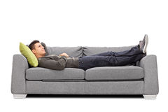 Pensive young guy laying on a sofa Stock Photos