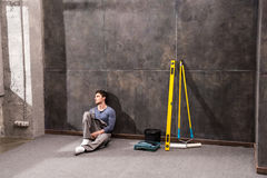 Pensive young laborer sitting on floor and looking away. Renovation concept Stock Photos