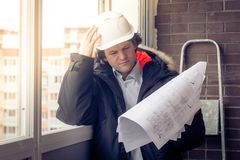 Pensive young man builder in hard hat standng and thinking. Soft focus, toned. Royalty Free Stock Image