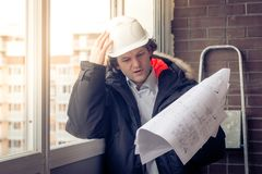 Pensive young man builder in hard hat standng and thinking. Soft focus, toned. Stock Images