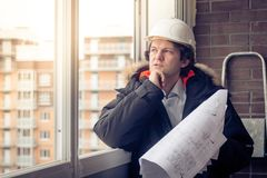 Pensive young man builder in hard hat standng and thinking. Soft focus, toned. Pensive young man builder in hard hat standng and thinking. Soft focus, toned Royalty Free Stock Images