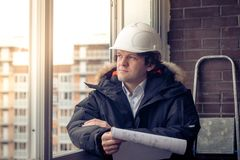 Pensive young man builder in hard hat standng and thinking. Soft focus, toned. Royalty Free Stock Images