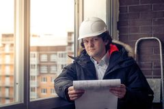 Pensive young man builder in hard hat standng and thinking. Soft focus, toned. Pensive young man builder in hard hat standng and thinking. Soft focus, toned Royalty Free Stock Image