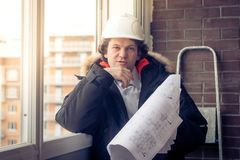 Pensive young man builder in hard hat standng and thinking. Soft focus, toned. Stock Image