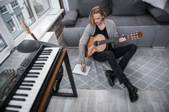 Inspired male musician creating melody. Pensive young man is composing song at home. She is writing words into the notebook with inspiration while sitting on Royalty Free Stock Images