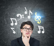 Pensive young man composing a tune. Close up of a pensive young composer wearing a suit and glasses and thinking about his new masterpiece to be. Blackboard Royalty Free Stock Image