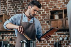 Pensive young man cooking. With tablet royalty free stock image